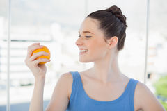 Cheerful slender woman in sportswear holding orange Royalty Free Stock Image