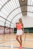 Cheerful slim sportswoman standing in indoor tennis court Stock Image