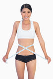 Cheerful slim woman measuring her waist Stock Images