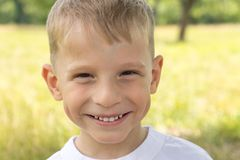 Cheerful small boy at summer park smiling looking straight into camera. Caucasian child at outdoor Stock Photos