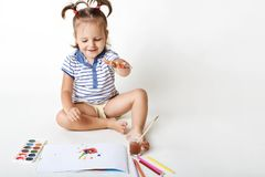 Cheerful small female kid draws with watercolour, makes fingerprints, has fun alone, likes to paint, isolated over white. Background. Creative little girl makes stock photos