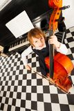 Cheerful small girl in dress playing on the cello Stock Photo