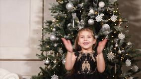 Little girl is blowing on sparkling confetti in hands, against Christmas tree. Cheerful small girl is holding confetti and blowing on it, enjoying, smiling and stock video footage