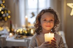 Free Cheerful Small Girl Standing Indoors At Christmas, Holding Candle. Royalty Free Stock Photography - 164409517