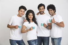 Cheerful small group of young people posing with coffee royalty free stock photography