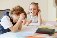 Cheerful small students share the same desk. Royalty Free Stock Images
