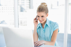 Cheerful smart businesswoman on the phone while using laptop Stock Images