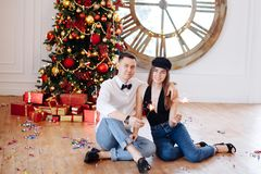 Cheerful smart couple with sparkler flirting near decorated Christmas tree at home before party stock photo