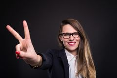 Cheerful smart girl doing peace sign. Cheerful smart girl with glasses doing peace or victory sign isolated on dark background Stock Images