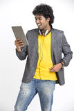 Cheerful smart Indian young urban man standing with tablet and  headphone. On white background Royalty Free Stock Photography