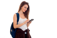 Cheerful smart student girl in brown sport clothes with backpack on her shoulders looking at her mobile phone and Royalty Free Stock Photo