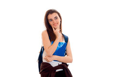 Cheerful smart student girl in brown sport clothes with backpack on her shoulders smiling and looking away isolated on Royalty Free Stock Photography