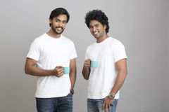 Cheerful smart young male smiling with cup of coffee. Two cheerful smart young male smiling with cup of coffee on grey background Royalty Free Stock Images