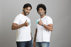 Cheerful smart young male smiling with cup of coffee. Two cheerful smart young male smiling with cup of coffee on grey background Stock Photography