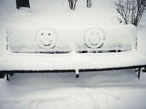 Cheerful smiley face drawn on a snow-covered bench. Two cheerful smiley face drawn on a snow-covered bench royalty free stock images
