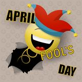 A cheerful smiley with a spring in a jester`s cap suddenly jumps out of a wall, tearing through a hole. Happy fools day. Vector illustration stock illustration