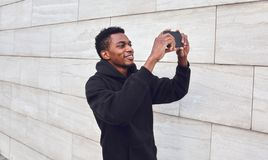 Cheerful smiling african man taking selfie picture by phone on city street over gray wall stock images