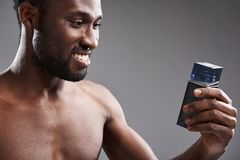 Joyful handsome afro American man holding his cologne stock photo