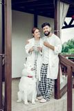 Cheerful smiling beaming happy adult married couple standing outdoors. Morning outdoors. Cheerful smiling beaming happy adult married couple in stylish pajamas stock image