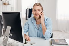 Cheerful smiling bearded male student recieves call from friend, sits at light office, dressed in blue shirt, finishes. Work soon. Handsome male freelancer has Stock Image