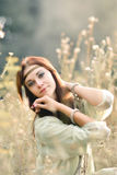 Attractive,charming,exquisite,lovely,red-haired girl in sunny summer field Royalty Free Stock Photo