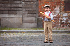Cheerful smiling boy with baguette outdoors Stock Photo