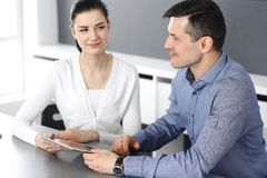 Cheerful smiling businessman and woman working with tablet computer in modern office. Headshot at meeting or workplace. Cheerful smiling businessman and women stock photography