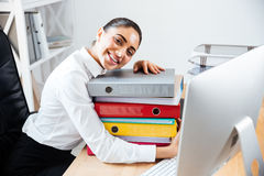 Cheerful smiling businesswoman laying on the stack of colorful folders Stock Photography