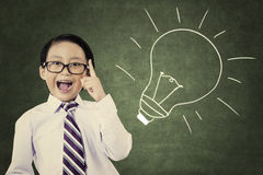 Cheerful smiling child at the blackboard. Portrait of cheerful smiling school student with lightbulb picture on blackboard Stock Images