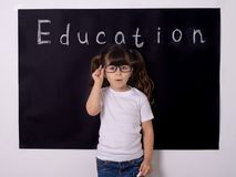 Cheerful smiling child at the blackboard. School concept. Clever kid in school. Back to school. Smart kid. School kid holding supplies royalty free stock image