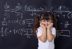 Cheerful smiling child at the blackboard. School concept. Studying kid. Pupil with glasses near black blackboard. Studio shoot, Cute kid back to school. Little stock image