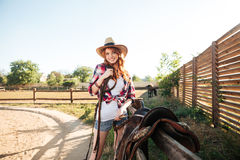 Cheerful smiling cowgirl preparing horse saddle for a ride Royalty Free Stock Images