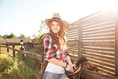 Cheerful smiling cowgirl preparing horse saddle for a ride Royalty Free Stock Photo