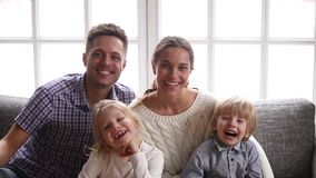 Cheerful smiling family with two kids laughing looking at camera