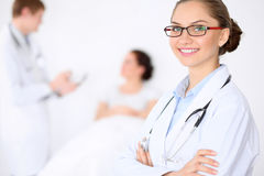 Cheerful smiling female doctor on the background with doctor and his patient in the bed. High level and quality of. Medical service concept Royalty Free Stock Image