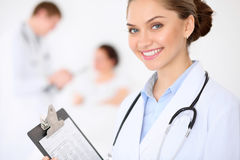Cheerful smiling female doctor on the background with doctor and his patient in the bed. High level and quality of. Medical service concept Stock Images