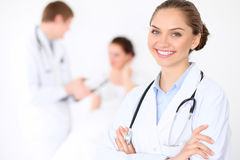 Cheerful smiling female doctor on the background with doctor and his patient in the bed. High level and quality of Royalty Free Stock Images