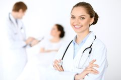 Cheerful smiling female doctor on the background with physician and his patient in the bed Royalty Free Stock Image
