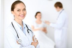 Cheerful smiling female doctor on the background with physician and his patient in the bed Royalty Free Stock Images