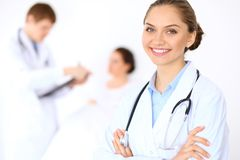 Cheerful smiling female doctor on the background with physician and his patient in the bed. High level and quality of medical service concept Royalty Free Stock Images