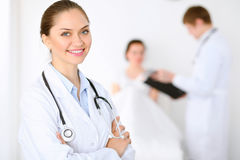 Cheerful smiling female doctor on the background with physician and his patient in the bed. High level and quality of Stock Photography
