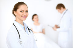 Cheerful smiling female doctor on the background with physician and his patient in the bed. High level and quality of medical service concept Stock Image