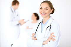 Cheerful smiling female doctor on the background with physician and his patient in the bed Stock Image