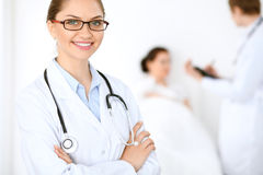 Cheerful smiling female doctor on the background with physician and his patient in the bed Stock Images