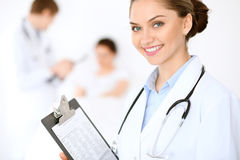 Cheerful smiling female doctor on the background with physician and his patient in the bed Stock Photography