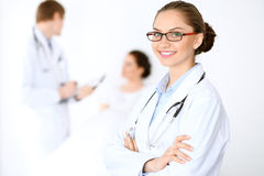 Cheerful smiling female doctor on the background with physician and his patient in the bed Stock Photo