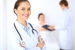 Cheerful smiling female doctor on the background with physician and his patient in the bed. High level and quality of medical service concept Royalty Free Stock Photo