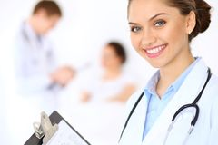 Cheerful smiling female doctor on the background with physician and his patient in the bed. High level and quality of medical service concept Royalty Free Stock Image