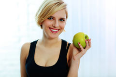 Cheerful smiling fit woman holding green apple Royalty Free Stock Photo