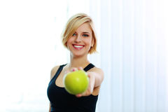 Cheerful smiling fit woman holding green apple Stock Image